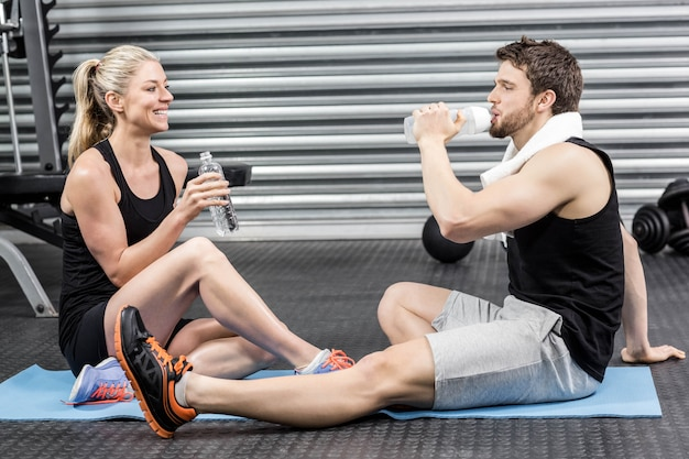 Couple sitting on fitness mat at crossfit gym