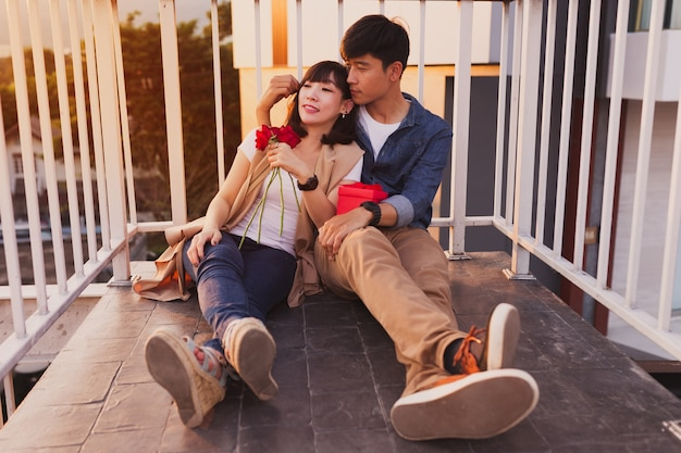Couple sitting on the floor leaning on a fence