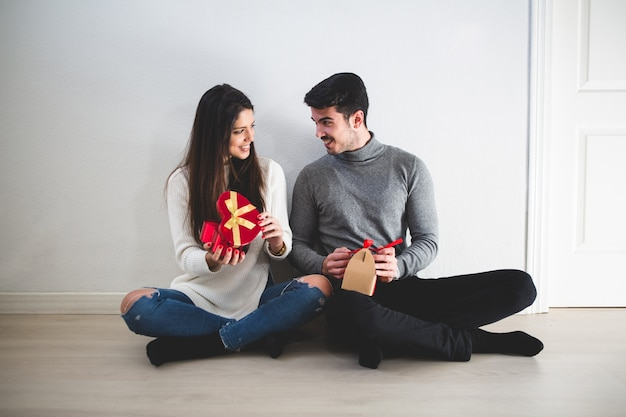 Couple sitting on the floor and she with a red gift