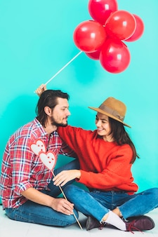 Couple sitting on floor with balloons and hearts on stick