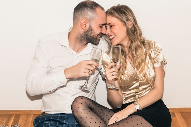 Couple sitting on floor with champagne glasses