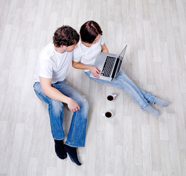 Coppia seduta sul pavimento con il computer portatile nella stanza vuota