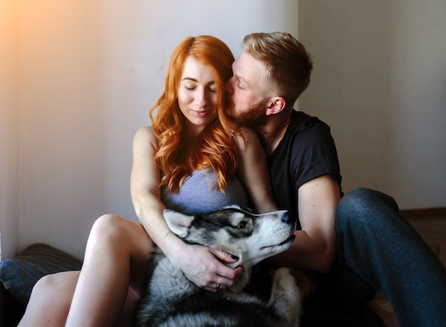 Couple sitting on the floor with their dog