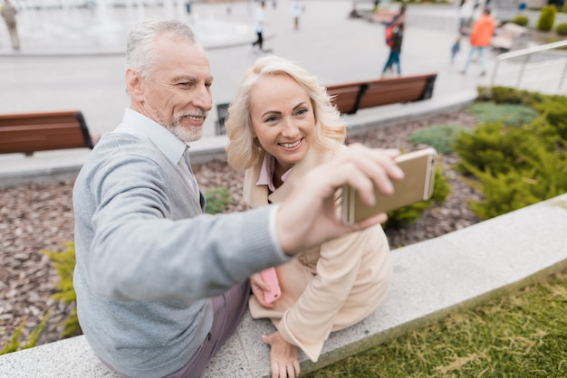 Couple sitting in flowerbed and making selfie together.