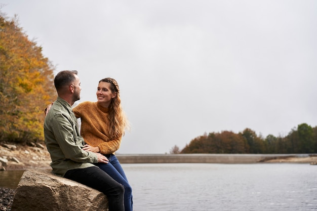 Couple sitting in front of the lake and looking at each other outdoors with a lake