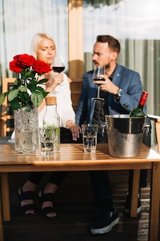 Couple sitting in front of wine bottle in an ice bucket on table with roses