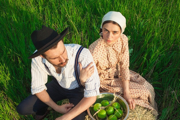 Couple sitting on the grass with apple basket