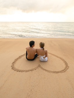 Couple sitting in heart drawing on sand beach relaxing sunbathing.