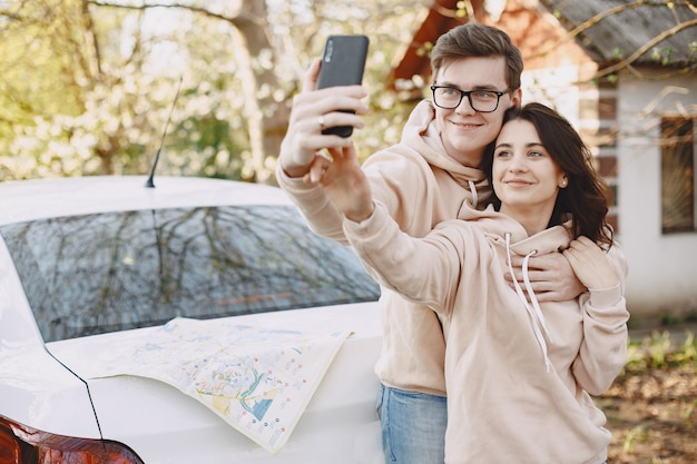 Couple sitting on a hood of car in a park