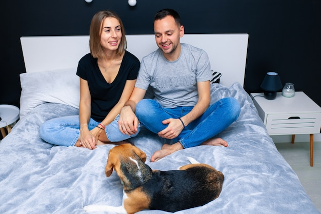 Пара сидит в спальне со своей собакой