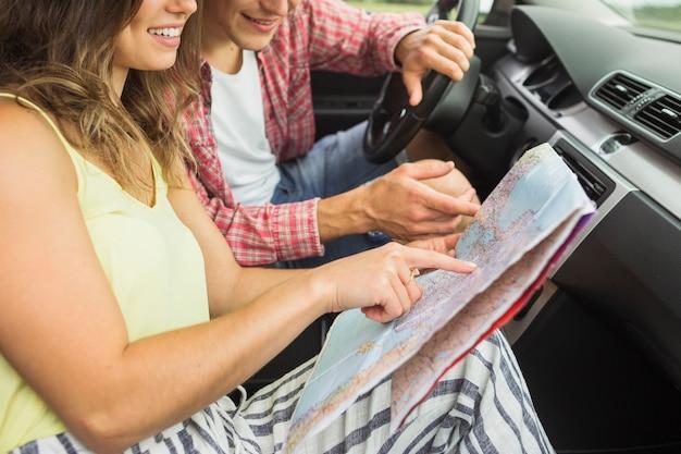 位置のナビゲーション地図上に指を指す車に座っているカップル