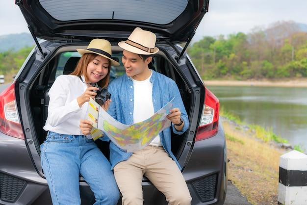 カメラで写真を探して、地図を保持している男女の車に座っているカップル
