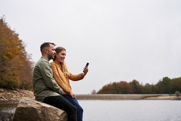 Пара сидит на берегу озера, делает селфи