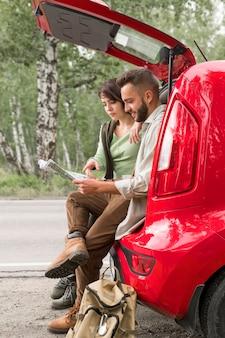 地図を見てトランクに座っているカップル
