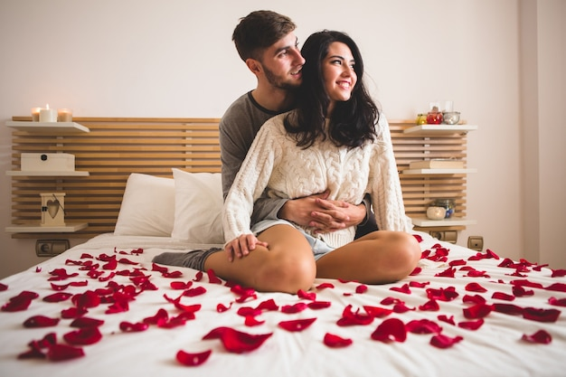 Couple sitting on knees on a bed with petals