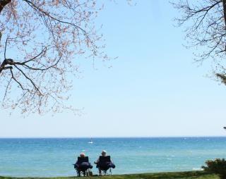 Couple sitting at lake ontario, oshawa