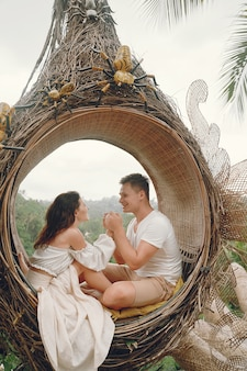 Couple sitting in a large nest on a bali