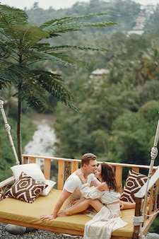 Couple sitting on a large swing on a bali
