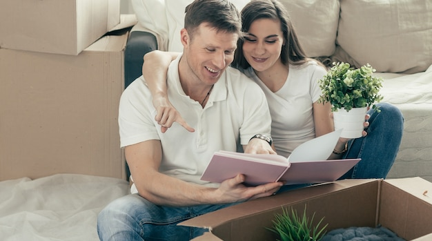 Пара сидит, глядя на семейные фотографии на полу в новой квартире