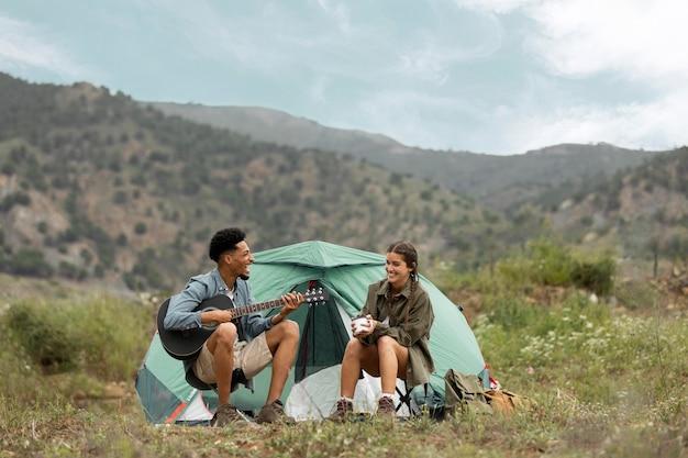 커플 텐트 전체 샷 근처에 앉아