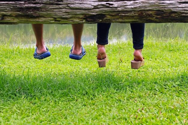 Пара, сидя рядом друг с другом на бревне - романтическая концепция