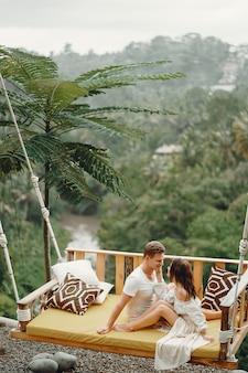 Пара сидит на больших качелях на бали