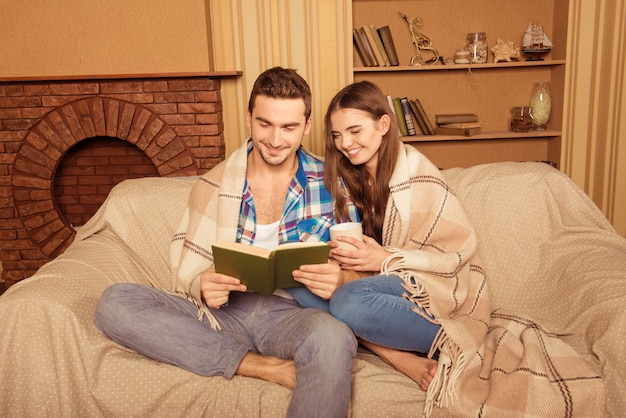 Пара, сидя на диване с книгой