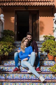Couple sitting on beautiful stairs outside