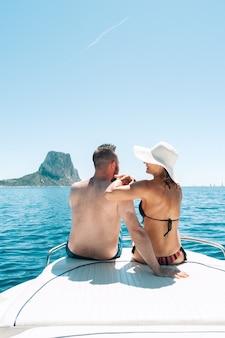 Пара, сидя на лодочной палубе, наслаждаясь видом на средиземное море