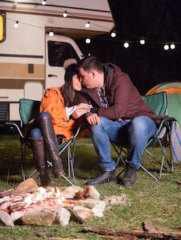 暖かいキャンプファイヤーの近くの秋の寒い夜にキャンプチェアに座っているカップル。電球付きのレトロなキャンピングカー。