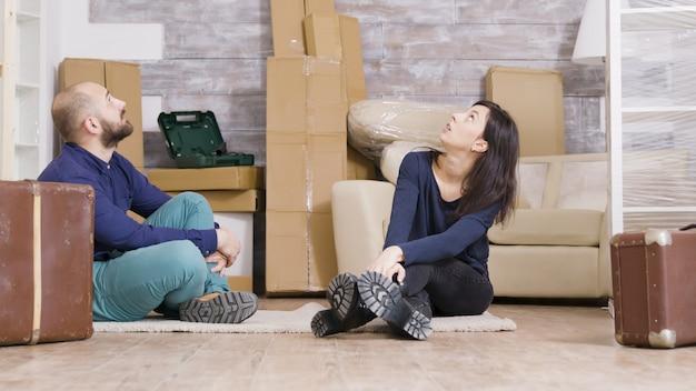 彼らの前にスーツケースを持って彼らの新しいアパートのカーペットの上に座っているカップル。バックグラウンドで段ボール箱。