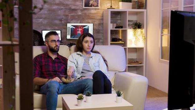 夜にテレビで映画を見ながらソファに座ってチップを食べるカップル。