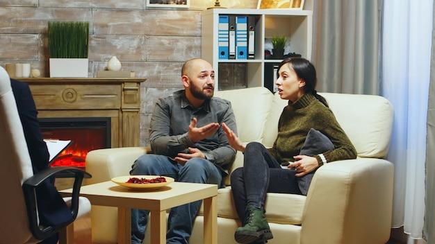 소파에 앉아 서로의 관계 문제에 대해 논쟁하는 커플. 메모를 하는 정신분석가.