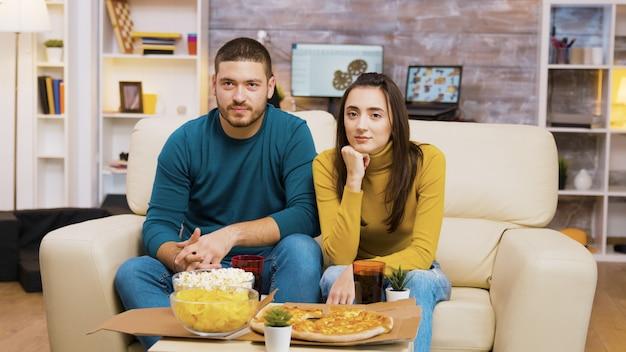 소파에 앉아 tv를 보고 피자를 먹으면서 웃고 있는 커플. 커피 테이블에 팝콘과 피자입니다.