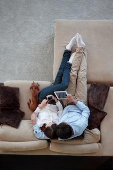 Пара, сидя на диване со своей собакой