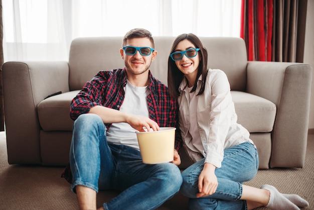 Пара сидит на полу и смотрит телевизор с попкорном