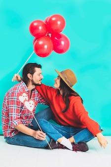 Пара сидит на полу с красными воздушными шарами и сердца на палочке