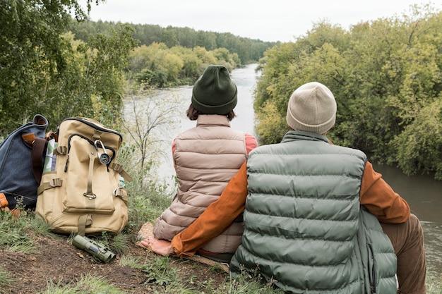 Пара сидит на земле, глядя на реку