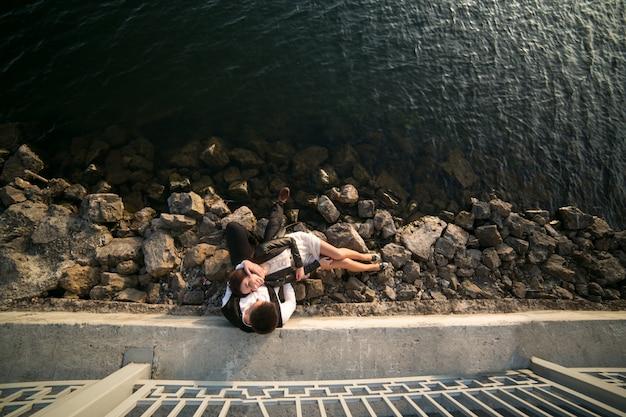 上から見た海の岩の上に座ってカップル