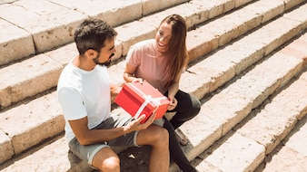 Couple sitting on staircase with red gift box
