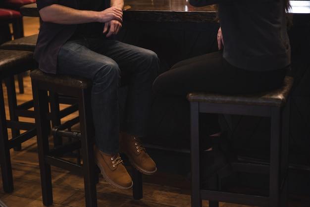 バーカウンターで椅子に座っているカップル