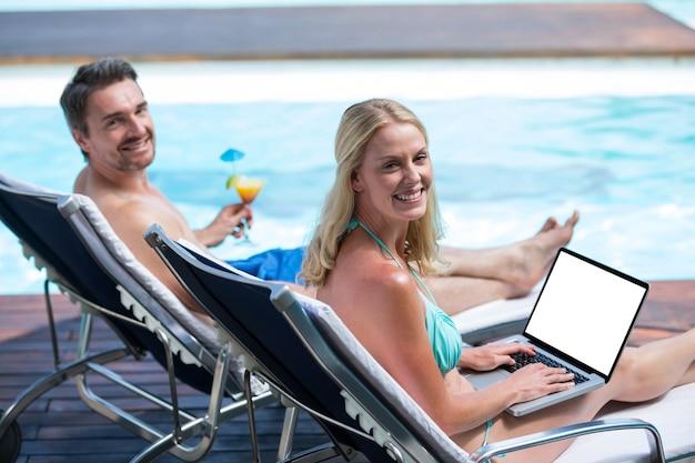プールの近くのサンラウンジャーに座っているカップル