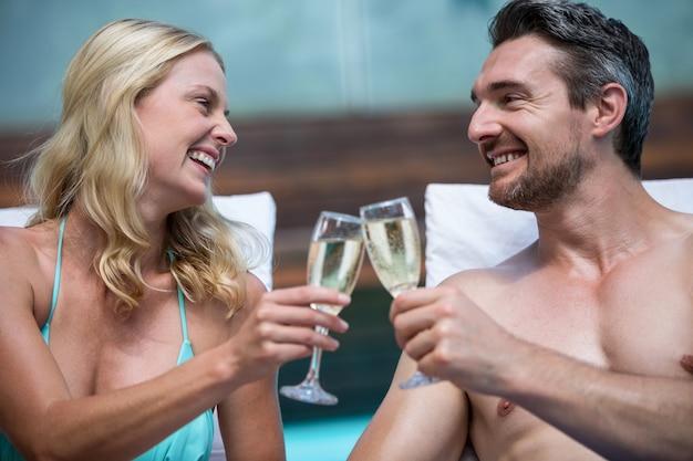シャンパンを乾杯するサンラウンジャーに座っているカップル