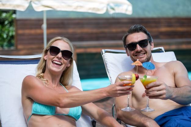 Пара, сидящая на шезлонге, поджаривающая коктейль