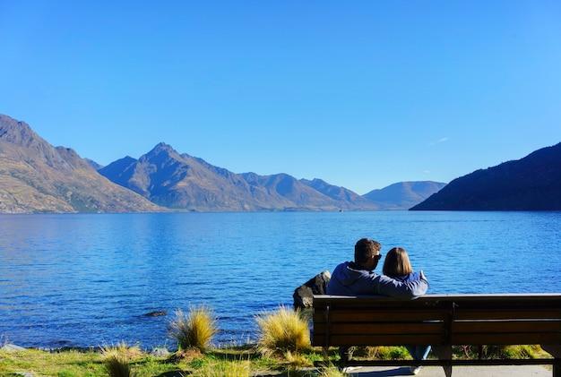 ニュージーランドの南島、クイーンズタウン、秋のワカティプ湖の雰囲気でリラックスしながら、クイーンズタウンガーデンの椅子に座っているカップル