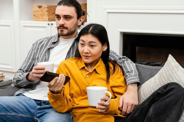 Пара сидит на диване и смотрит телевизор