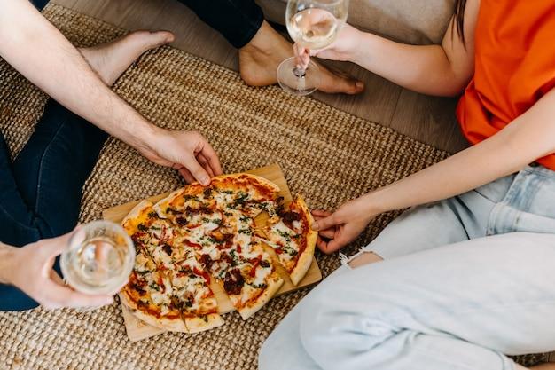 Пара сидит на полу, ест пиццу и пьет вино