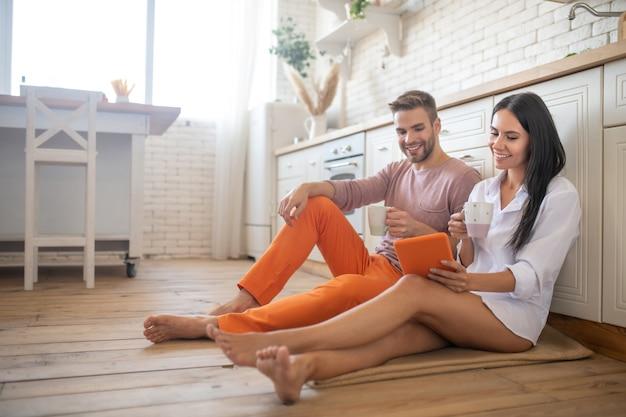 커피를 마시고 태블릿에서 영화를 보는 동안 바닥에 앉아있는 커플