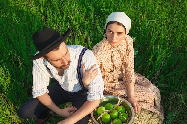 リンゴのバスケットと草の上に座っているカップル