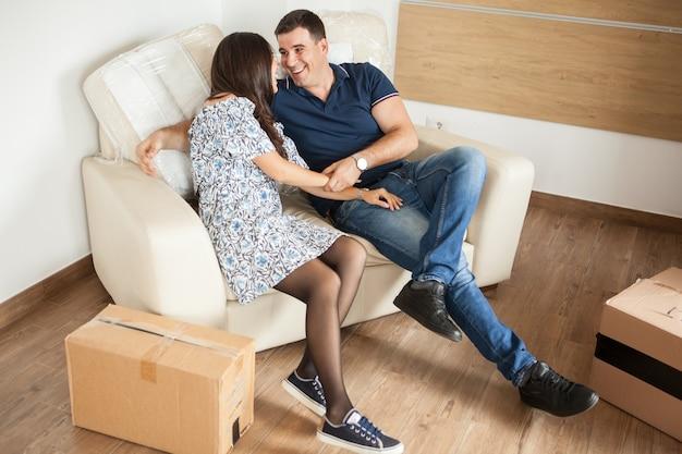 彼らの新しい家のソファに座っているカップル。一緒にリラックスする愛らしいカップル